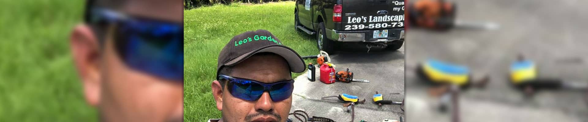 The owner of Leo Garden Care wearing a Leo Garden Care hat, standing in front of a truck bearing the company's logo.