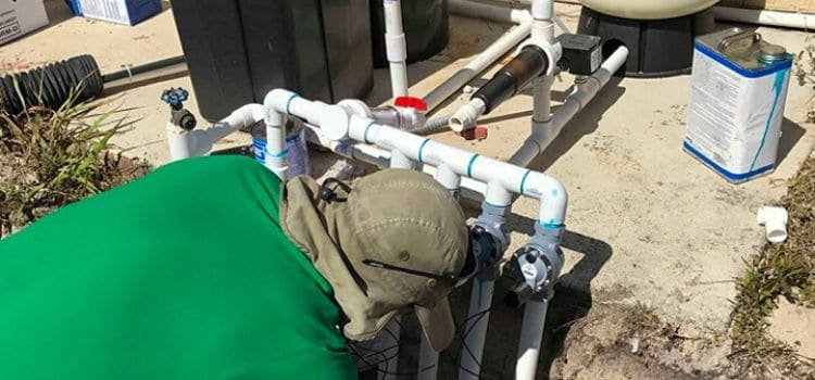 An employee of Leo's Garden Care working on a irrigation system to ensure maximum efficiency.