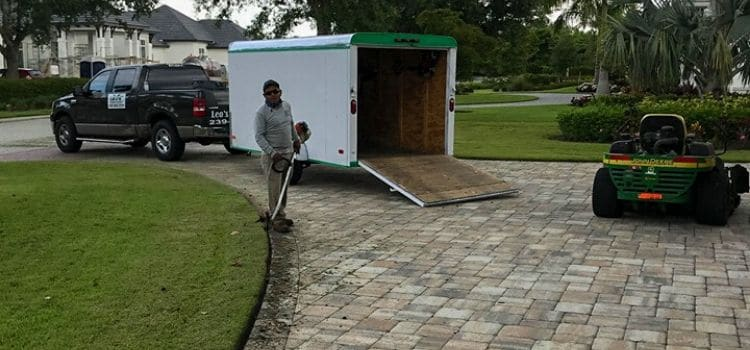 A Leo's Garden Care employee neatly edging a driveway.