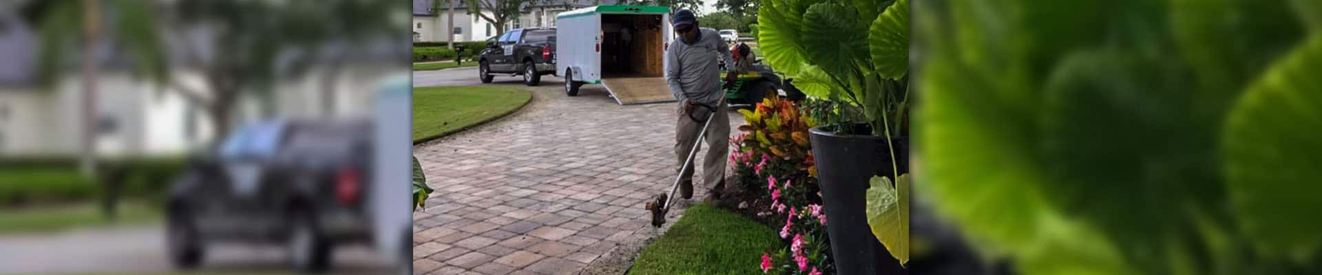 Employee of Leo Garden Care using a stick edger to complete lawn care service.
