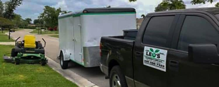 A black truck connected to a trailer. The truck has a Leo Garden Care logo on the side. Beside the truck and trailer is a large zero turn lawn mower.